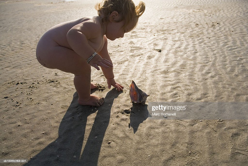 Naked baby girl (9-12 months) bending down next to seashell on beach : Foto stock