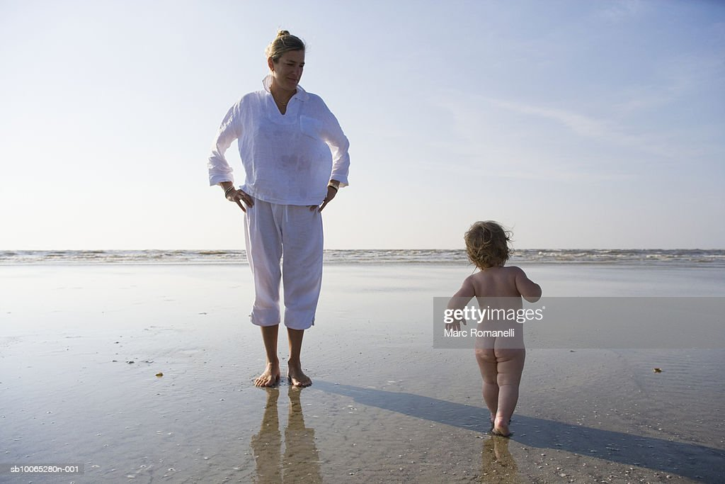 Naked baby girl (9-12 months) running by woman on beach : Foto stock