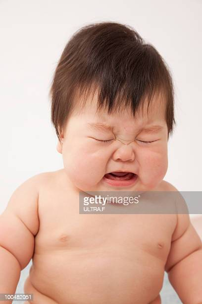 A naked baby is crying.