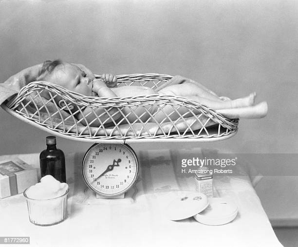 Naked Baby Laying On A Light Colored Wicker Scale On Top Of Table With Cotton Swabs Tissues & Toiletries Care Health Comfort Nursery.