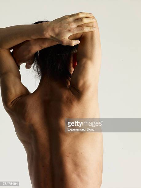 Naked back of a young man with his hands up