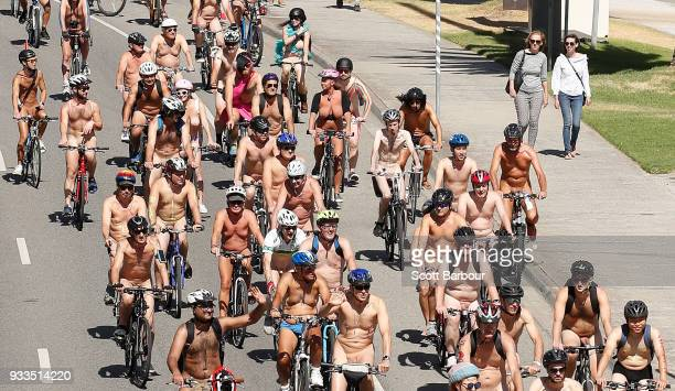 Naked bike riders cycle past two women walking down the street during the 2018 Naked Bike Ride on March 18 2018 in Melbourne Australia The World...