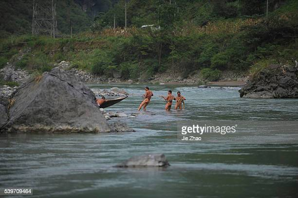 Naked boat trackers are seen along the Shennong Brook at a photo opportunity in Badong county Hubei province September 12 2010 The boat trackers'...