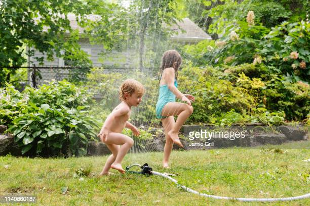 naked boy and his sister playing with sprinkler - bambine femmine nudi foto e immagini stock