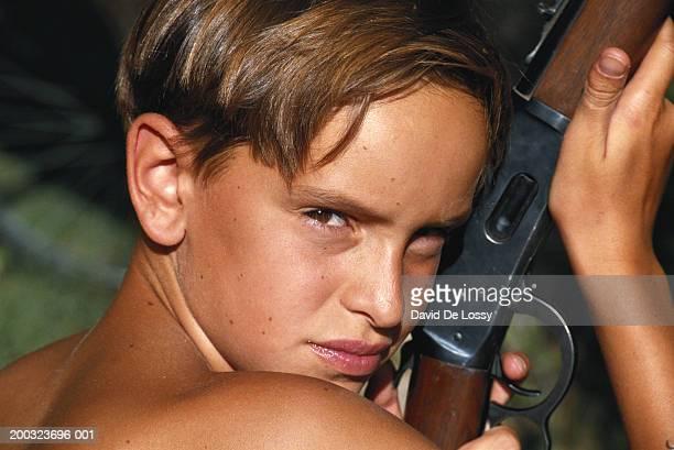 Naked boy (8-9) holding rifle, close-up