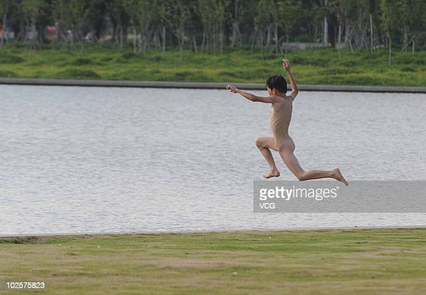 A naked boy jumps into a river to keep cool on July 1 2010 in Foshan Guangdong Province of China The local temperature reaches 358 degree centi...
