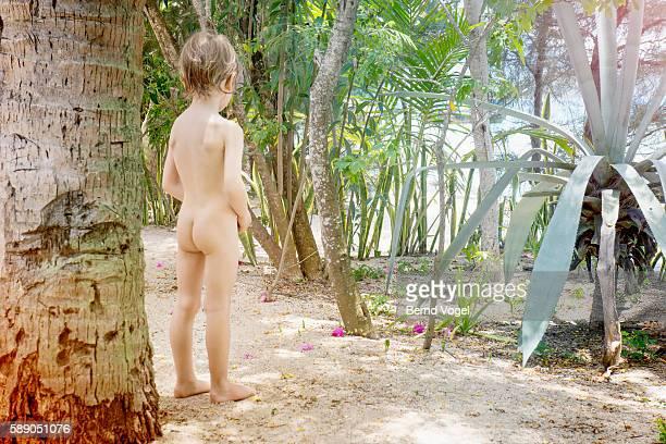 Naked boy (4-5) standing on sandy beach