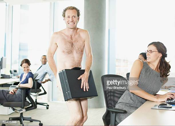Naked businessman with briefcase in office