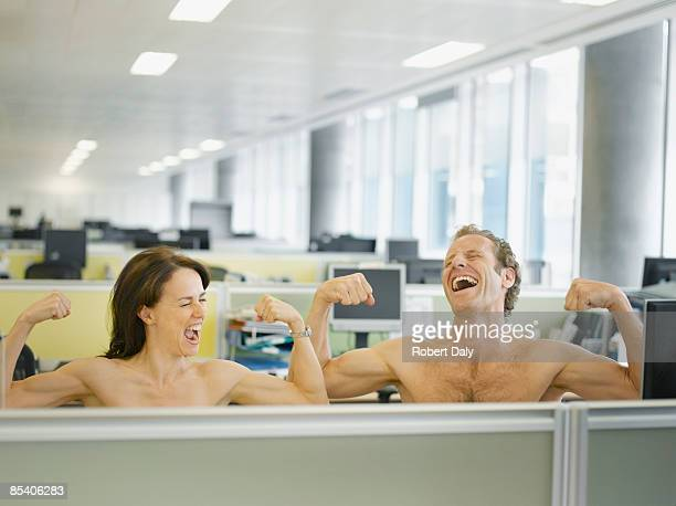 naked businesspeople flexing muscles in office - naturism stock photos and pictures