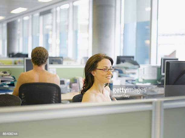 Naked businesspeople working in office