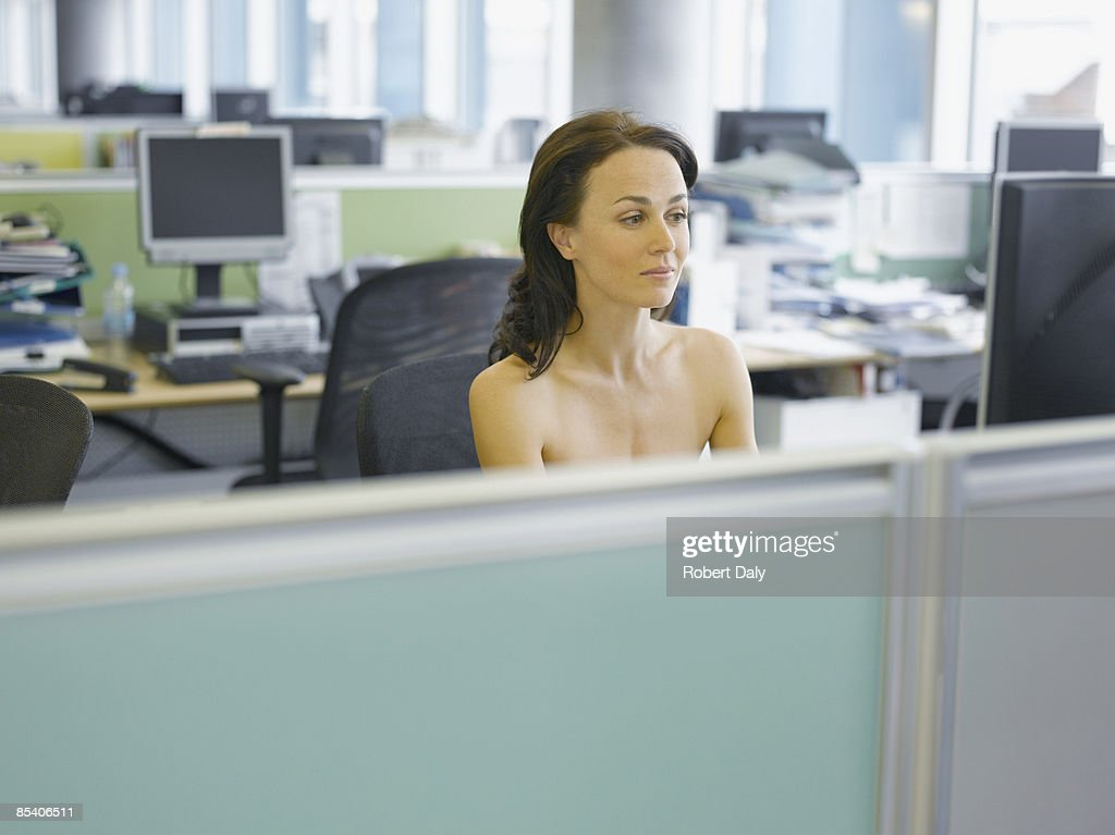 Naked businesswoman working at desk : Stock Photo