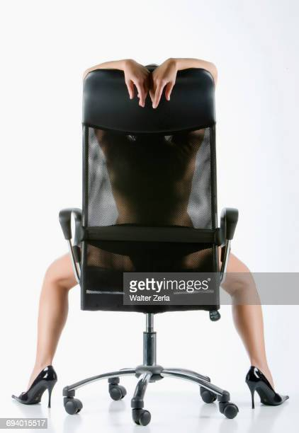 Naked Caucasian woman wearing high heels in office chair