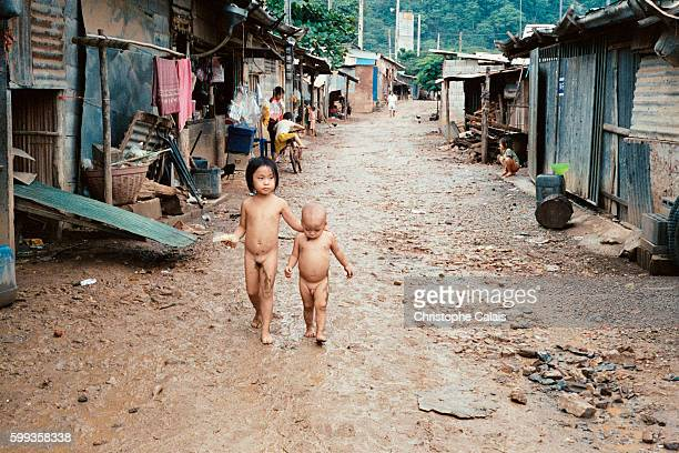Naked children walk through the muddy streets of the Wat Tham Krabok refugee camp Situated 150 km north of Bangkok the camp houses 16000 Laos' Hmong...