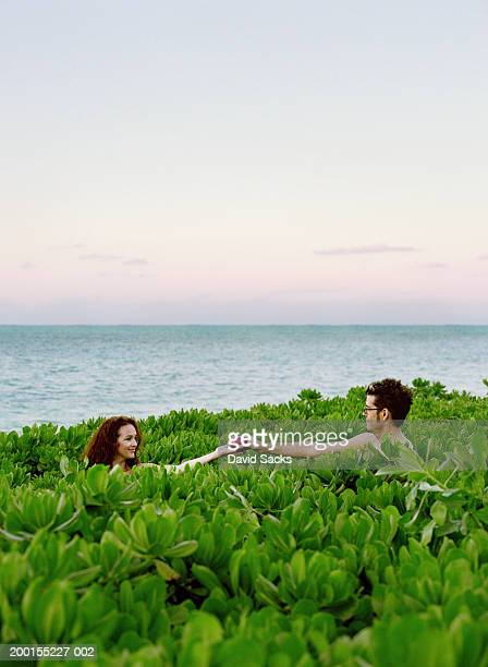 Naked couple holding apple in tropical plant field