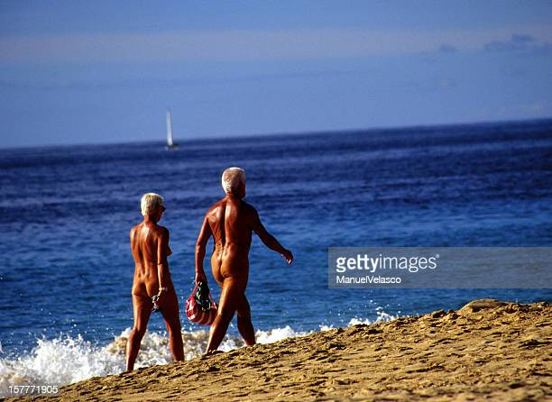 naked couple on the beach - naturalist beach stock photos and pictures