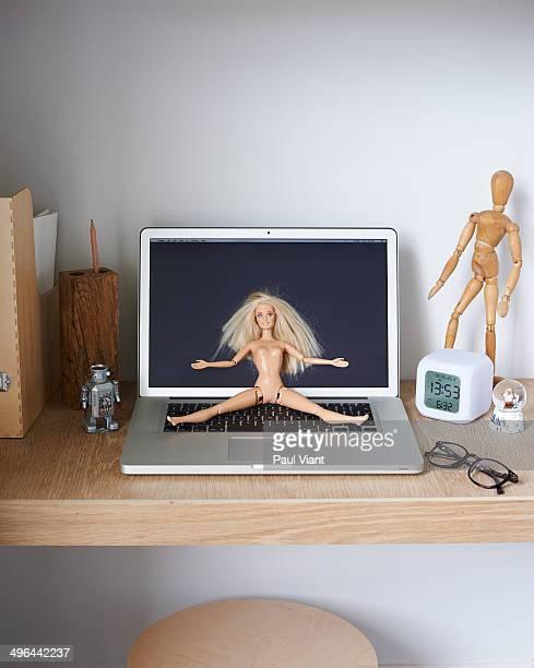 Naked doll on laptop keyboard