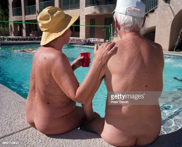 A naked elderly couple sit by an outdoor swimming pool at the Desert Shadows Inn Resort for nudists