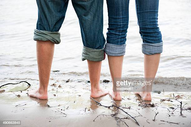 Naked feet of young couple standing in the water of Rhine river