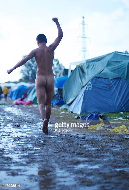 A naked Festival goer runs through the camp site during heavy rainfall on day three of Roskilde Festival 2011 on July 2 2011 in Roskilde Denmark