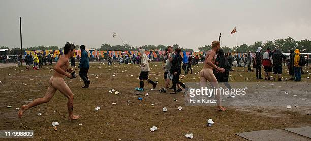 Naked Festival goers run through the Orange Stage area during heavy rainfall on day three of Roskilde Festival 2011 on July 2 2011 in Roskilde Denmark