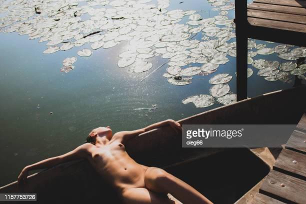 naked girl lies in a boat - nuda foto e immagini stock