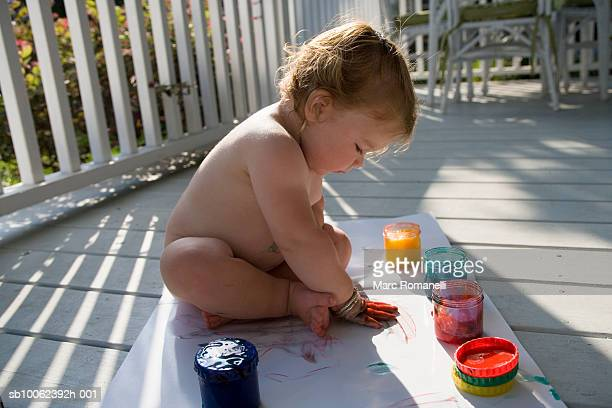 Naked girl (9-12 months) painting on porch