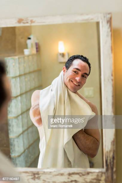 Naked Hispanic man drying with towel in mirror