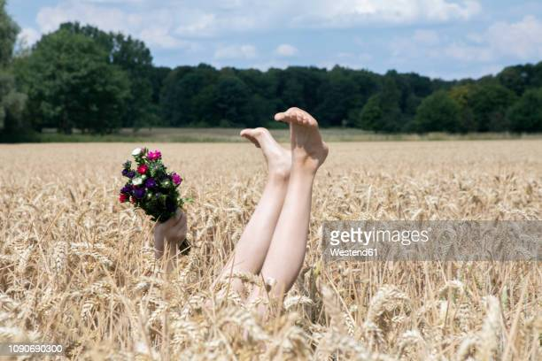naked legs of girl and hand holding bunch of flowers in a field - bambine femmine nudi foto e immagini stock