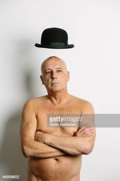 Naked magician making his hat fly