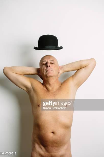 naked magician making his hat fly - senioren aktfotos stock-fotos und bilder