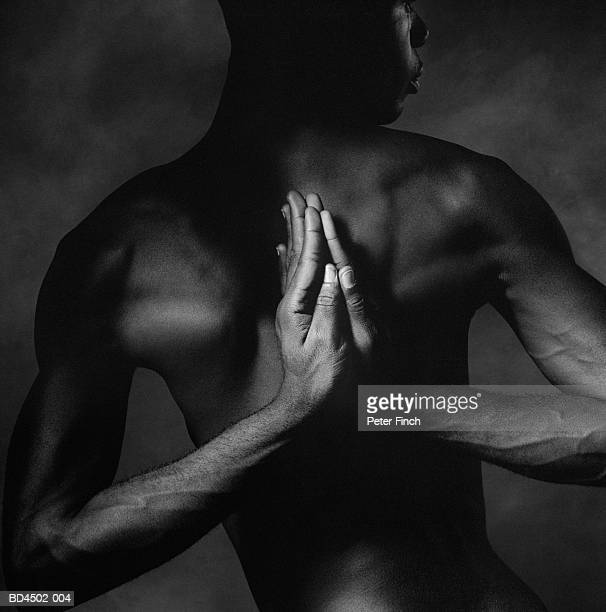 Naked male contortionist, palms pressed together behind back (B&W)