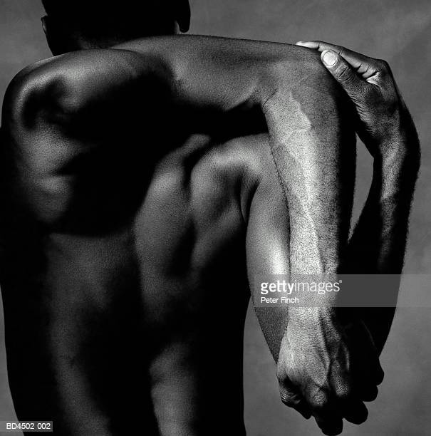 Naked male contortionist, twisting arm behind head, rear view (B&W)