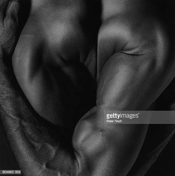 Naked male contortionist, twisting arms behind back, rear view (B&W)