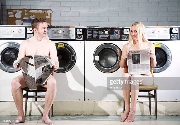 naked man and woman reading newspaper at the laundromat - funny nude women stock pictures, royalty-free photos & images