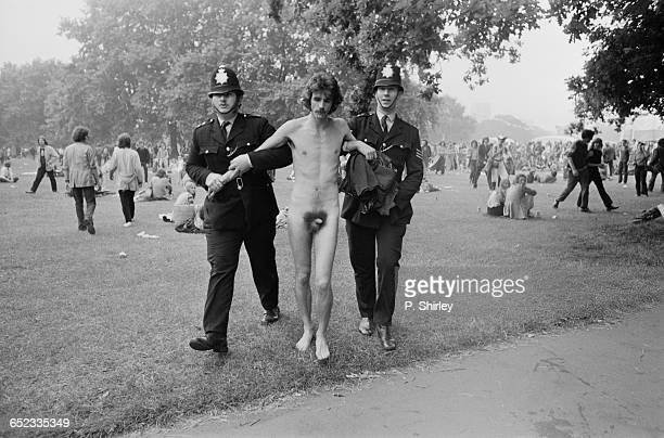 A naked man being escorted away by police at the Hyde Park music festival London UK 3rd July 1971