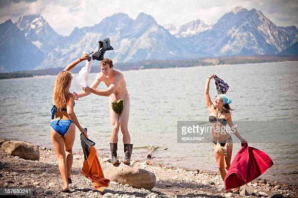 naked man getting his clothes stolen by two girls - skinny dipping stockfoto's en -beelden