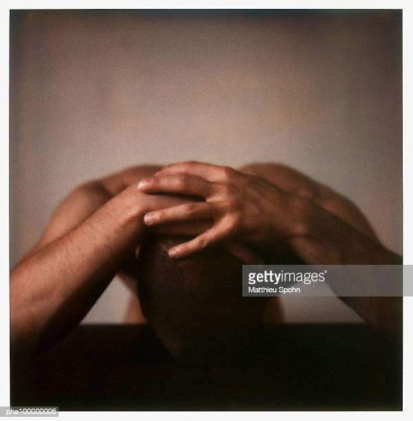 Naked man, head down, hands folded on top of head, close-up