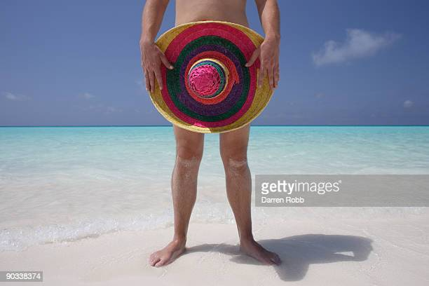 Naked man holding a sombrero on tropical beach