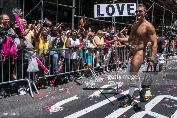 A naked man holds a sign during the annual New York Gay Pride Parade in Fifth Avenue on June 25 2017 in New York City