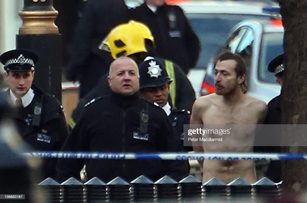 A naked man is detained by police after standing at the top of a statue in Whitehall on November 23, 2012 in London, England. The incident in central London has brought traffic to a standstill as Police attempted to talk the man down from the Duke of Cambridge statue outside the Ministry of Defence building.