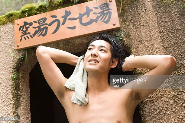Naked man looking up and holding a towel, hot spring, front view, Japan