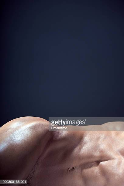 Naked man lying on side, twisting hip, mid section