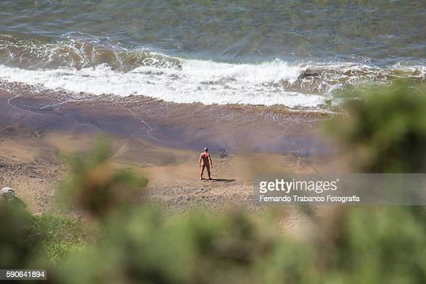 naked man on the beach ( elevated view) - nudisten stock-fotos und bilder