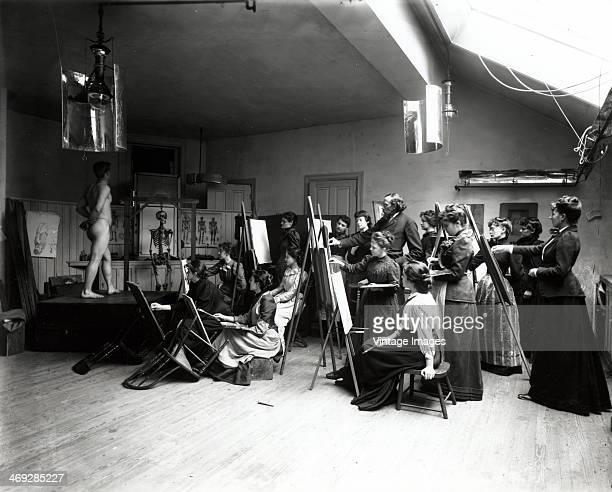 A naked man poses for a roomful of ladies at a life drawing class circa 1900