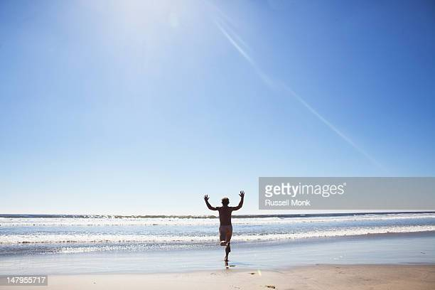 A naked man running into the ocean