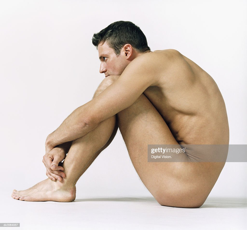 Naked Man Sitting Down With His Arms Around His Knees : Stock Photo