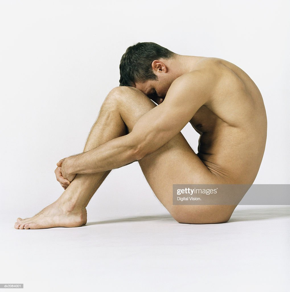 Naked Man Sitting With His Hands Around His Knees : Stock Photo