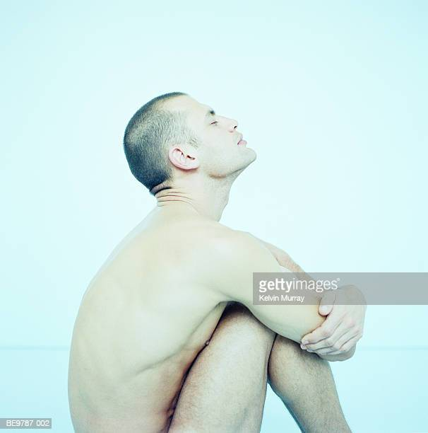naked man sitting with knees to chest, eyes closed, profile - naakte man en profiel stockfoto's en -beelden