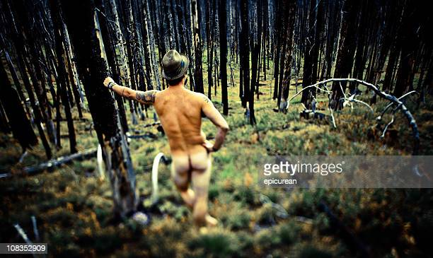 Naked man standing alone in a burned down forest