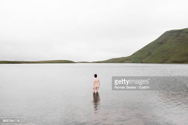 naked man standing in lake against sky - bare bottom stock pictures, royalty-free photos & images